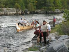 Lining and poling Montreal Canoe up the French River Rapids.