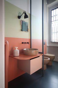 une salle de bain au design épuré couleur blush et vert au sol noir