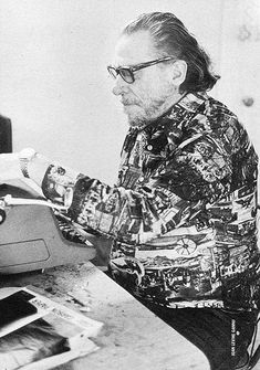 Photographs of Charles Bukowski Feeding another sheet into the SG-1 typer, 1970s
