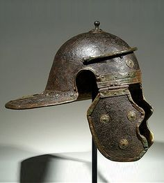 Roman Legionary iron and bronze helmet of the Mainz- Weisenau type (side view). Many of the appliques had a purpose other than decorative: they helped reinforce the helmet and deflect blows. Now in the Merrin Gallery in New York. Helmet Armor, Suit Of Armor, Ancient Armor, Medieval Armor, Roman Artifacts, Ancient Artifacts, Roman Helmet, Roman Armor, Roman Legion