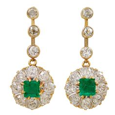 Elegant diamond and emerald antique drop earrings set  in 18K yellow gold  The emeralds are approx 1ct total weight. The diamonds are approx 3 1/2ct. The full- cut diamonds surround the brillant colored emerald -cut emeralds. c. 1905