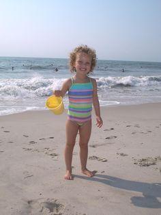Nella foto sono da solo alla spiaggia. Avevo cinque anni. Giocacvo nella sabbia e favevo i castelli di sabbia. Non sono cambiata da quando ero piccola perche' quando vado alla spiaggia, faccio i castelli di sabbia. Assomigliavo mia madre perche' aveva i capelli ricci. Portavo il costume da bagno e avevo i capelli corti e ricci. Ero sulla spiaggia.  Faceva caldo c'era il sole. Mi sentivo ecciatata. Ho giocato sulla spiaggia.