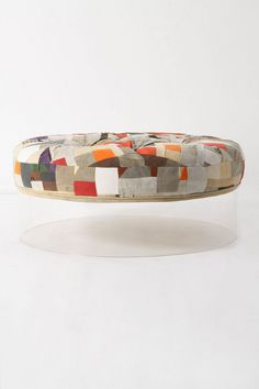 "Riley Ottoman, Anthropologie. ""A tufted pouf of patchworked truck tarp swatches seems to hover colorfully just above the ground. Look again and you'll notice the mod Lucite base below."" Cool."