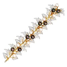 Tiffany & Co. Schlumberger 18K Gold Platinum Cultured Pearl Diamond Bracelet. The flexible foliate band, the leaves set with round diamonds weighing approximately 10.00 carats, accented by white and gray cultured pearls measuring approximately 9.0 to 8.5 mm, length 7 inches, signed Tiffany & Co., Schlumberger.