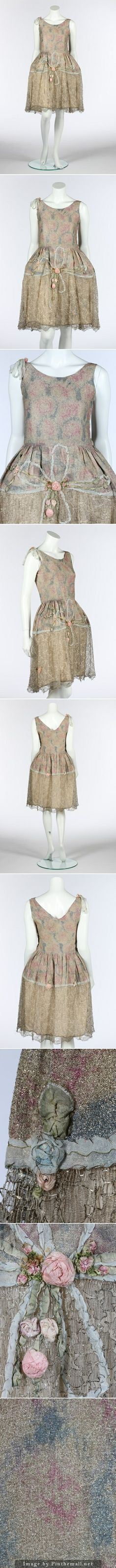 A printed lame robe de style, mid 1920s. the silver ground with mottled pink and blue floral ground, the skirt with large ribbon-work bow and flowers above a silver tulle flounce, with internal hooped net panniers. KTA