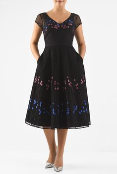 Sheer tulle embellished with graphic florals is styled with a wide V-neckline, princess seamed bodice, banded waist and full skirt for a flattering silhouette.