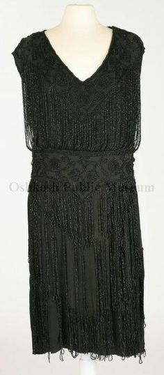 circa 1920s, Black crepe, V-neck, sleeveless dress with a V-shaped band extending from the shoulders to center of bodice front and across the shoulders on bodice back. Band is decorated with black beads .