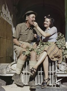 An Eighth Army soldier enjoys being fed grapes by a local girl in Sicily August 1943.