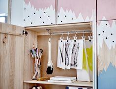 Armarios IVAR con un mural de color azul, blanco y rosa. Armario abierto que deja ver su interior.