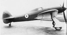 """The unarmed first prototype Typhoon P5212 taken just before its first flight. The prototype had a small tail unit and a solid fairing behind the cockpit, which was fitted with """"car door"""" style access hatches; no inner wheel doors were fitted and the Sabre engine used three exhaust stubs either side of the cowling."""