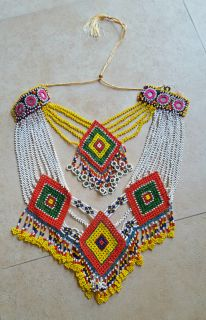 This is a colorfully hand-beaded custom made necklace from Afghanistan.Each bead used in the construction is hand sewn to create a piece of art using a bright color combination.The necklace is very light weight.  Necklaces like these are worn daily by Kuchi women to enhance their notoriously colorful clothing and flamboyant accessories.        Length = 22 inches neckline circumference as currently tied (can tie longer or shorter)      Front Drop = 8-1/4 inches      Material = Glass beads…