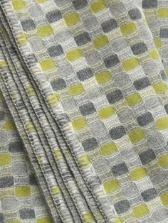 Shingle.-  Named for its colour and for the shingle beach in Dorset, this design is a study in chalky greys with a hint of citrus yellow. 100% wool.  Colour: greys, white and citrus yellow.    Blanket stitch edging in silver grey. Standard size: 150 x 180 cm £230.00. Long size: approx 150 x 240 cm £296.00.