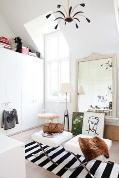 a fashion forward dressing room.  barcelona stools, striped rug, and over-sized vintage mirror.  christine ralphs.