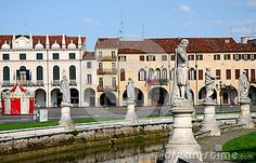 Photo made in Prato della Valle in Padua in Veneto (Italy). In the picture you see, in the foreground, the statues that form a double ellipse on the banks of the river that borders the island Memmia. In the picture you can also see the water inside the ring of concrete and historical buildings in the background. To the left of the bright colors of a small carousel stand in front of the white wall of the building that is at the back.
