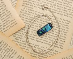 Diochroic necklace - these are really easy to wear and add a little colour to your outfit. Made from melted glass and carefully constructed into these designs. Against a background of old book pages makes for an interesting feature. #diochroicnecklace #diochroic #jewellery #jewelry #necklace #womens #fashion #blue #pages
