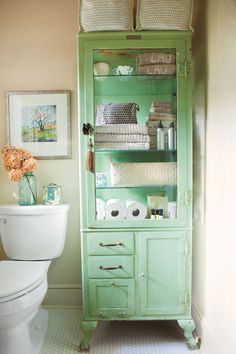 If built-ins aren't possible, add storage and style with an antique cabinet. This homeowner stores towels and toiletries in a green vintage dental cabinet.  See More of this Vintage-Style Home