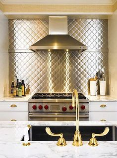 Behind the range, a stainless-steel backsplash stamped in a diamond pattern offers a gleaming counterpoint to white-painted cabinets and a marble-topped island.