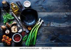 Top view of colorful organic vegetables and seasoning ingredients on rustic kitchen table with olive oil and balsamic vinegar. Healthy food or vegetarian food concept.