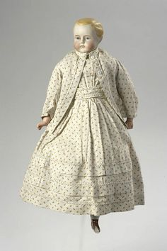 1868 Doll, moulded bisque shoulder head and lower legs with a stuffed cloth body, moulded composition arms, painted facial features and moulded hair painted blond; legs painted with copper lustre to represent heeled boots (one leg broken)  clothing:  dress and jacket, white cotton printed with yellow flecks  full petticoat and drawers, white cotton  flannel, with bodice of heavy cotton