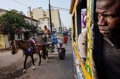 A horse lags behind one of Dakar's car rapide mini buses. Photo by Ricci Shryock #senegal