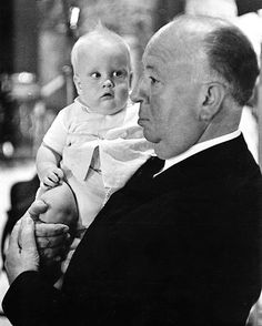 Alfred Hitchcock holding a baby during the filming of a cameo scene for TORN CURTAIN (1966).