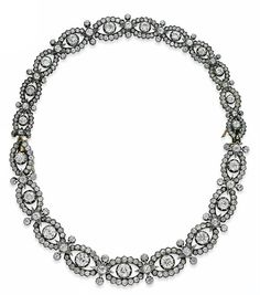 A LATE 19TH CENTURY DIAMOND NECKLACE PAIR OF BRACELETS  Designed as a series of diamond-set graduated oval shaped links, centred by old-cut diamond collets, with three point diamond-set panels between, circa 1880, 36.7cm long, mounted in silver and gold, original fitted case