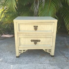 (Shipping is extra- If you would like a freight shipping quote, please contact me before buying. Thanks!) Vintage nightstand/end table. Shangri-La by Dixie. Hollywood Regency style. Beautiful fretwork detail at the bottom, as well as a fretwork border in the middle. Square brass feet with brass hinged drawer pulls. In its original speckled finish. Dovetail drawers. This piece is in good vintage condition with some cosmetic blemishes normal with age. There is some chipping in one small ar...