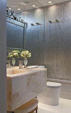 Um bloco de alabastro de 35 cm de altura compõe a cuba do lavabo, que se destaca entre espelhos. O de estilo veneziano veio da antiga sala da moradora. Nas demais paredes, papel com efeito de metal oxidado.