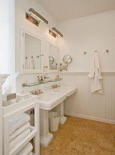 Picture light over medicine cabinet, glass shelf under cabinet, pedestal sink.
