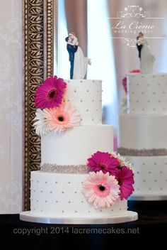Gerbera daisies add whimsy to this cute three tier buttercream wedding cake with edible silver pearls.