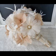 This romantic one of a kind Old Hollywood Style bouquet is sure to be a beautiful compliment to your wedding day! Perfect bouquet for your Gatsby, Vintage, Masquerade, Modern or Traditional wedding. Each flower is hand crafted with the best quality silky feathers and your choice silver or gold rhinestone brooches and pearls. The bouquet shown displays romantic shades of ivory and champagne and is accented with gold tone centerpieces. Also available with silver accents and can be made in…