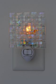 Light shines through and reflects off this dichroic chips fused glass night light beautifully, changing with movement and in different lighting conditions. The glass was fused in my kiln and is a 3 square. The glass was attached to a night light fixture with an on/ off switch, so that the light can be turned on and off, as needed! No more falling down the stairs or turning on glaring overhead lights to move about during the night