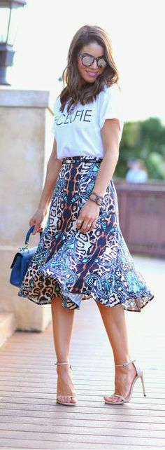 Camila Coelho com camiseta branca básica e saia midi estampada de animal print e sandália de tiras.