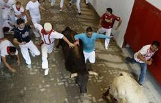 Runners sprint alongside Dolores Aguirre fighting bulls at the entrance to the bull ring during the second running of the bulls of the San Fermin festival in Pamplona July 8, 2013. Click on to see more pics from San Fermin...