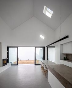 The interior features a minimal material palette, with surfaces including the microcement floors, limestone countertops and wooden joinery adding textural details throughout. Divider, House, Ceiling Lights, Gallery, Room, Furniture, Home Decor, Bedroom, Decoration Home