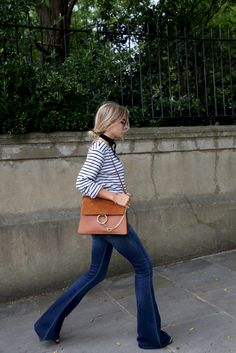 Thin Black Chocker Scarf, Black and White Striped Long Sleeve Shirt, Rusted Orange Leather Bag With Gold Hardware, Dark Blue Flared Jeans