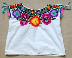 colorfully embroidered girl's blouse is part of the traditional costume from the area of Sibaca Chiapas, a Tzeltal Maya region of Mexico