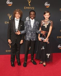 Get Your Fashion Fix Straight From the Emmys Red Carpet Gaten Matarazzo, Caleb McLaughlin, and Millie Bobby Brown Millie is wearing a REDValentino dress, a bespoke Edie Parker clutch, and Nicholas Kirkwood shoes.