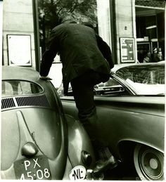 1960's. Man tries to enter car parked in front of the department store De Bijenkorf on Dam in Amsterdam. Photo Dolf Toussaint. #amsterdam #1960 #DeBijenkorf #Dam