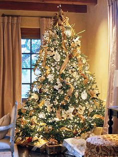 Golden Christmas Tree:   Laced with golden ribbon, clear lights, and gold wire flower- and dove-shape ornaments, this tree has an antique glow that's sure to remind you of past holiday seasons.