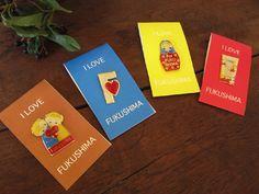 """""""福島発信プロジェクト、福島から4つのメッセージ。写真の左から「子ども達の未来」(茶)、「福島からのメッセージ」(青)、「エネルギーの考え方」(黄)、「自然の大切さ」(赤)をカタチにしたピンバッジです。"""""""