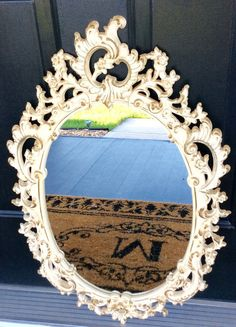 This is a unique rare vintage Syroco oval mirror. Ornate floral & scroll design, done in a ivory & gold original finish. This is a Syroco product stamped on back of frame & made of a sturdy resin composite material in the USA! In very good to excellent vintage condition, no scratches on mirror ( perfect condition). Has two metal hooks with cord for hanging! Stunning statement wall decor, wedding decor, bedroom or nursery decor. Would go with so many home decors whether you love Hollywood…