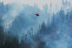 Helicopters drop water on the Blue Creek wildfire as it burns near Walla Walla, Wash., July 22, 2015. Officials warn about the potential for even more catastrophe in the months ahead, as drought, heat and climate change leave the landscape ever thirstier. (Ruth Fremson/The New York Times)