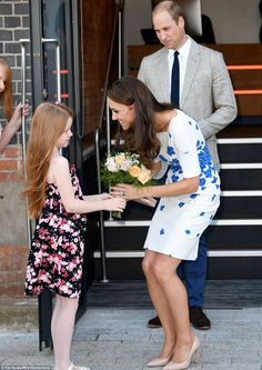 8/24/16*Prince William watches on as the Duchess of Cambridge receives flowers from a young girl outside the centre