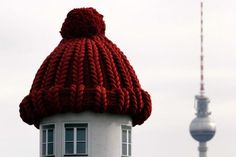 Advertising pillar of a house crowned with a woollen hat
