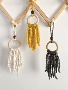 Adorable set of 3 mini yarn wall hangings. Can be used together or separate. Perfect for small spaces or even as an ornament. Handmade and designed by Bonnie at Wildly Boho with yarn on wood rings featuring wood bead detail. Yarn is thick, super soft and fluffy. Pefect for your car or in your office space at work. Measurements:  Full length: 11 in. Ring width: 2.5 in.  This item can be customized.  Follow my Instagram @wildlyboho