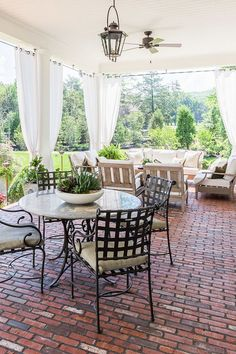 Brick floor porch with an outdoor living room and gauzy curtains.