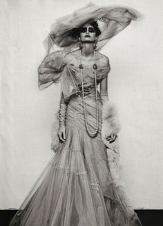 Taking inspiration from Steve Klein for Christian Dior, this Dia de los Muertos look would be fun to put together for a party. Find a thrifted bridesmaid, wedding or prom dress and pair it with a sun hat wrapped in tulle. Add elbow length gloves, pearls, a pair of door knocker earrings and a large flower to embellish. Finish the look off with black and white face paint.
