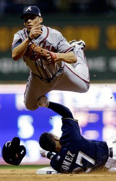 """""""Atlanta Braves' Andrelton Simmons leaps over Milwaukee Brewers' Carlos Gomez as he unsuccessfully tries to turn a double play Tuesday in Milwaukee. The Brewers blanked the Braves 5-0."""""""