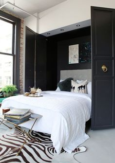 Chic Murphy bed.  Love the crisp white bedding and zebra print cowhide rug.